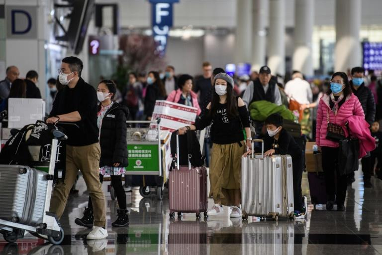 Passengers wear face masks at the  international airport in Hong Kong, where authorities have announced the first suspected case of the new SARS-like virus