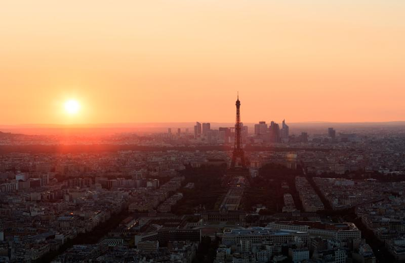 The sun sets behind the Eiffel Tower and the skyscrapers of La Defense business district in Paris, France.
