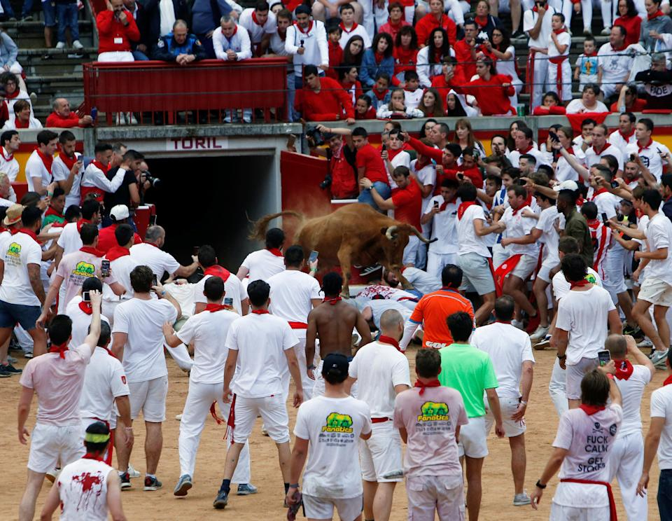 A wild cow leaps over revellers following the first running of the bulls at the San Fermin festival in Pamplona, Spain, July 7, 2018 (REUTERS)