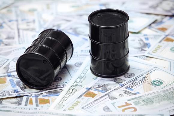 Two shiny, black oil barrels on top of U.S. currency.