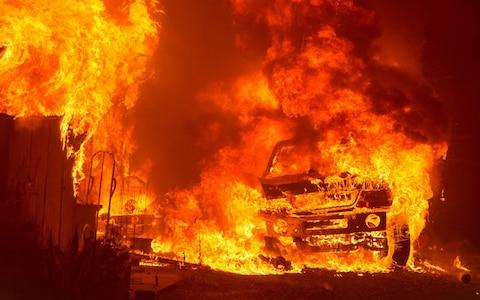 """A car and house are engulfed in flames as the """"Wall Fire"""" burns through a residential area in Oroville, California on July 8, 2017 - Credit: Josh Edelson/AFP"""