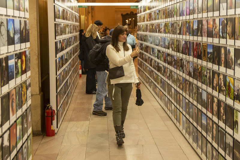 A woman documents the many rows of photos at the Fujifilm Printlife Photo Exhibit. (Photo: Gordon Donovan/Yahoo News)