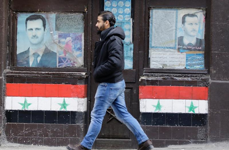 A Syrian man walks past posters of President Bashar al-Assad on a shop front in Damascus, on January 3, 2017 (AFP Photo/Louai Beshara)