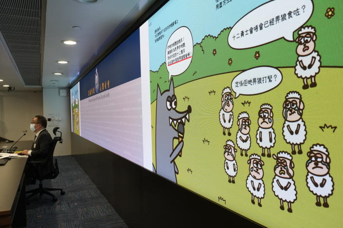 Li Kwai-wah, left, senior superintendent of Police National Security Department speaks in front of a screen showing evidence including the contents of three children's books on stories that revolve around a village of sheep which has to deal with wolves from a different village, before a press conference in Hong Kong Thursday, July 22, 2021. Hong Kong's national security police on Thursday arrested five people from a trade union of the General Association of Hong Kong Speech Therapists on suspicion of conspiring to publish and distribute seditious material, in the latest arrests made amid a crackdown on dissent in the city. (AP Photo/Vincent Yu)