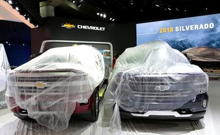Two 2018 Chevrolet Silverado pick-up trucks sit under plastic on the display floor before the start of Press Days for the North American International Auto Show at Cobo Center in Detroit