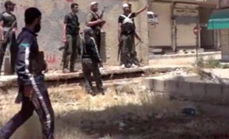 This image from amateur video obtained by a group which calls itself Ugarit News, which is consistent with AP reporting, shows rebel fighters in Daraa, Syria, Tuesday, May 28, 2013. Europe's decision to allow member states to arm Syrian rebels and Russia's renewed pledge to send advanced missiles to the Syria regime could spur an arms race in an already brutal civil war and increasingly turn it into a East-West proxy fight. Britain promises not to transfer any arms before diplomacy is given a chance in Syria peace talks expected next month, while a top rebel commander says he needs Western anti-aircraft and anti-tank missiles now to prevent more regime gains on the battlefield. (AP Photo/Ugarit News via AP video)