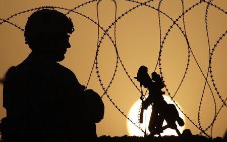 A US soldier keeps watch at sunset from Combat Outpost Terra Nova in the Arghandab Valley