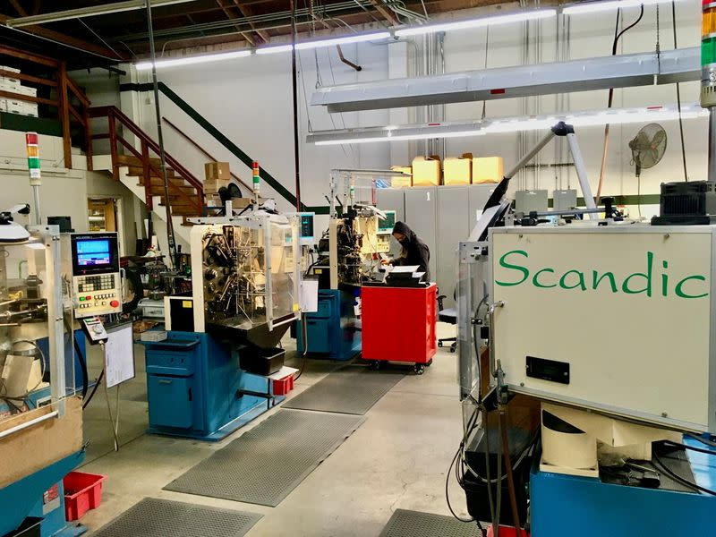 An operator programs a CNC wireforming machine to make a custom spring at Scandic Springs' factory in San Leandro