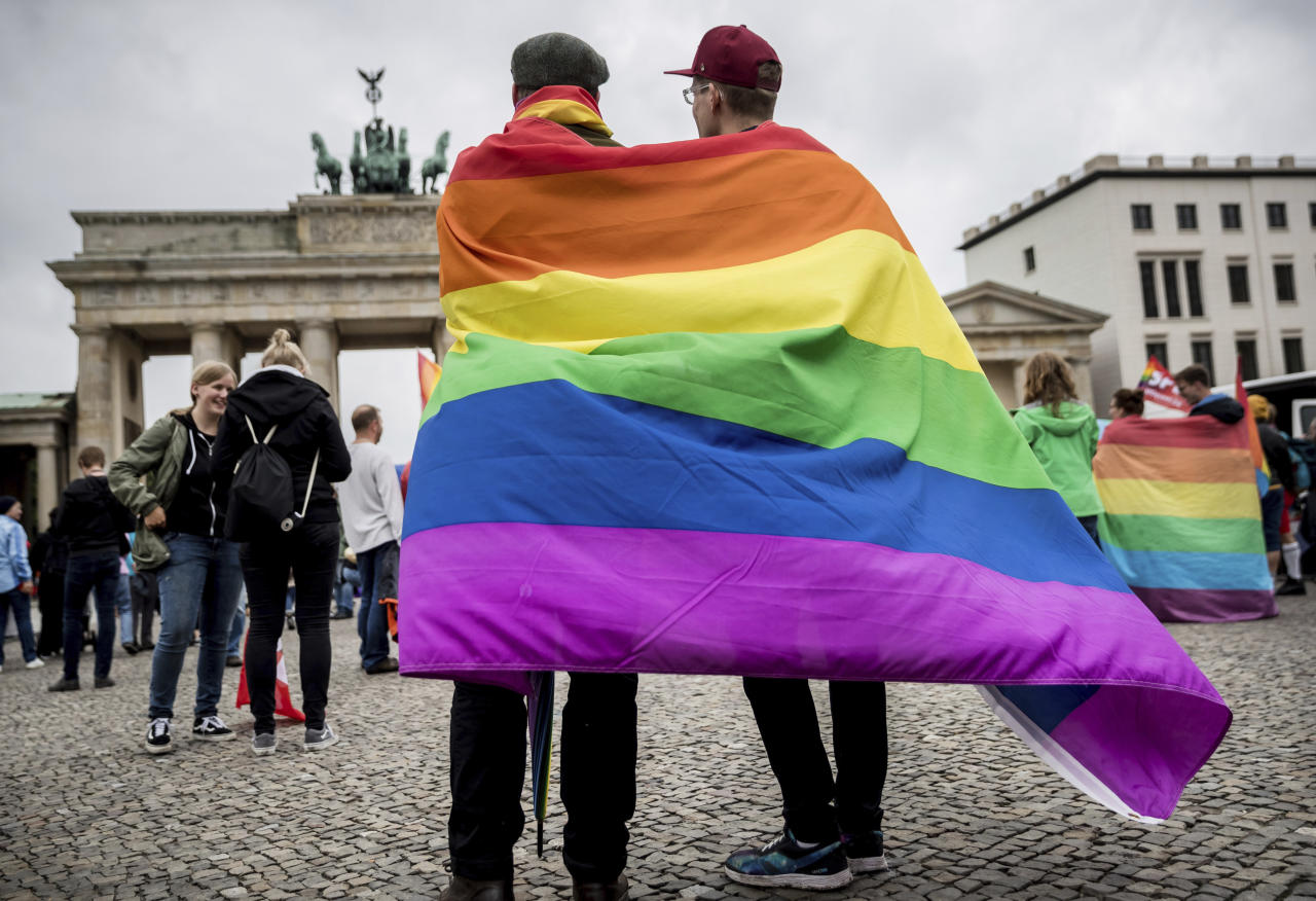CORRECTS TO GERMAN PRESIDENT SIGNED LEGISLATION THURSDAY JULY 20, 2017 - FILE - In this June 30, 2017 file photo, men with rainbow flags stand in front of the Brandenburg Gate at an event organized by the Social Democrats to celebrate the legalization of same-sex marriage in Berlin. Germany's president has signed legislation Thursday July 20, 2017 legalizing gay marriage, paving the way for it to take effect this fall.Lawmakers approved the bill on June 30 in its last session before Germany's September election. (Michael Kappeler/dpa via AP,file)