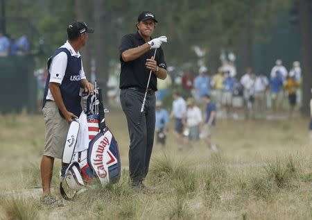 Phil Mickelson of the U.S. looks over his shot from the rough on the 12th hole during the first round of the U.S. Open Championship golf tournament in Pinehurst, North Carolina, June 12, 2014. REUTERS/Mike Segar