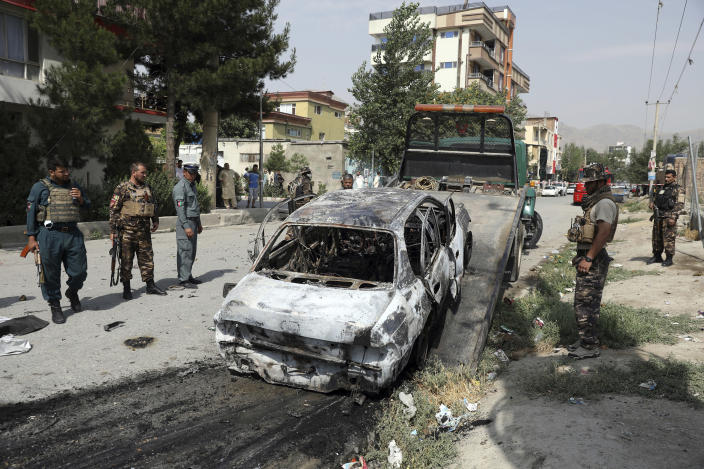 Afghan security personnel inspect a damaged vehicle which was firing rockets in Kabul, Afghanistan, Tuesday, July 20, 2021. At least three rockets hit near the presidential palace on Tuesday shortly before Afghan President Ashraf Ghani was to give an address to mark the Muslim holiday of Eid al-Adha. (AP Photo/Rahmat Gul)