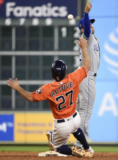 Kansas City Royals second baseman Whit Merrifield, right, misses the throw from shortstop Adalberto Mondesi during a double play attempt as Houston Astros' Jose Altuve (27) slides into second during the eighth inning of a baseball game Friday, June 22, 2018, in Houston. Mondesi was charges with an error on the play. (AP Photo/Eric Christian Smith)