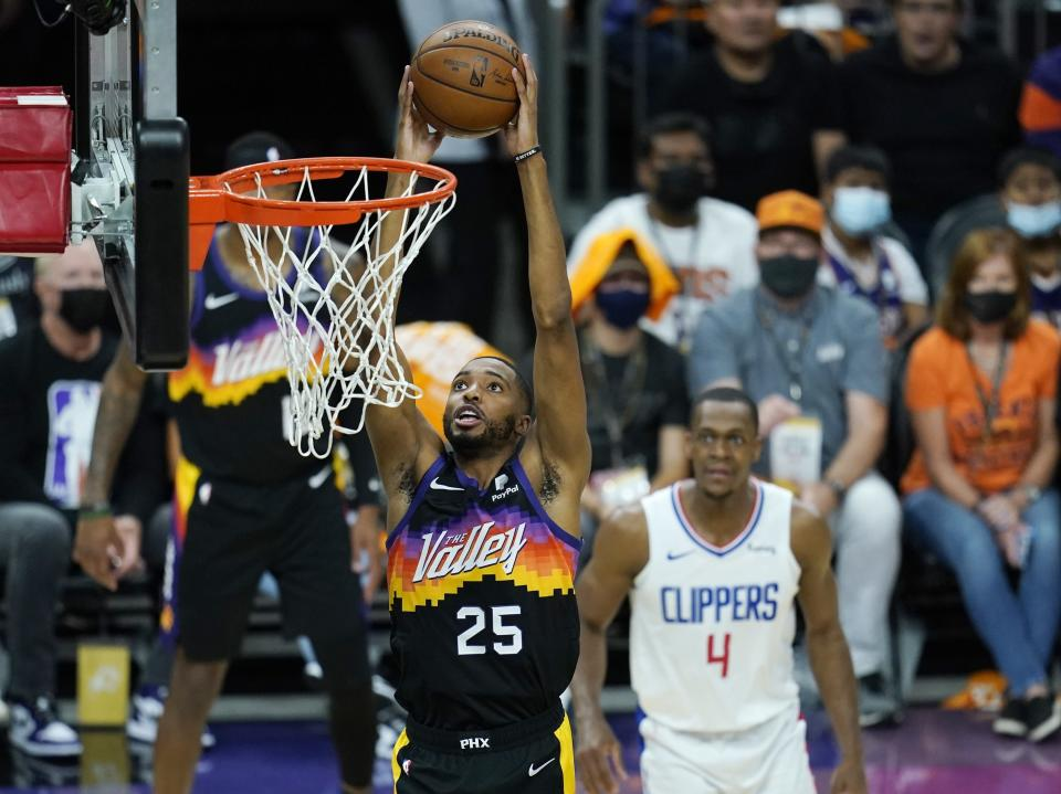 Phoenix Suns forward Mikal Bridges (25) goes in for a dunk as Los Angeles Clippers guard Rajon Rondo (4) looks on during the first half of Game 1 of the NBA basketball Western Conference finals Sunday, June 20, 2021, in Phoenix. (AP Photo/Ross D. Franklin)