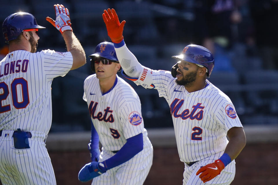 New York Mets' Pete Alonso (20) celebrates with Brandon Nimmo (9) and Dominic Smith (2) after Smith hit a two-run home run during the first inning of a baseball game against the Philadelphia Phillies in the first game of a doubleheader Tuesday, April 13, 2021, in New York. (AP Photo/Frank Franklin II)