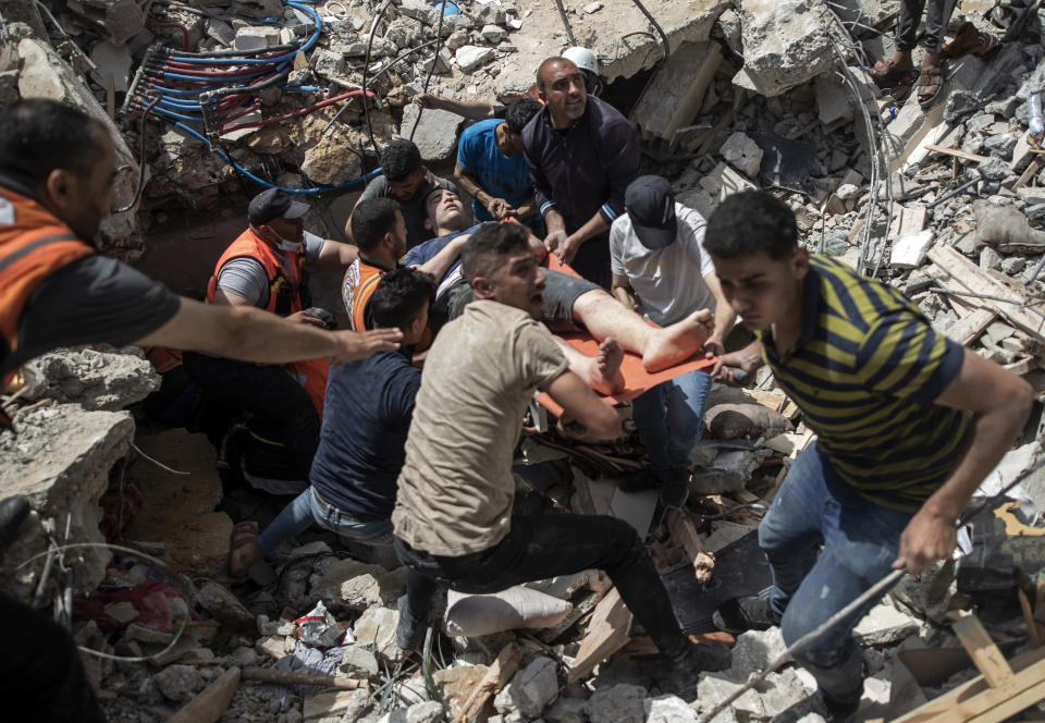 """FILE - In this May 16, 2021, file photo, Palestinian rescue a survivor from under the rubble of a destroyed residential building following deadly Israeli airstrikes in Gaza City. Human Rights Watch on Tuesday, July 27, 2021, accused the Israeli military of carrying attacks that """"apparently amount to war crimes"""" during an 11-day war against the Hamas militant group in May. (AP Photo/Khalil Hamra, File)"""