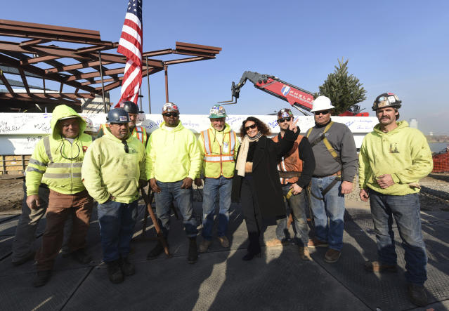 Diane von Furstenberg, fundraising chair for the new Statue of Liberty Museum, celebrates with construction workers at the Topping Off ceremony for the new Statue of Liberty Museum, Monday, Dec. 4, 2017, on Liberty Island in New York. (Diane Bondareff/AP Images)