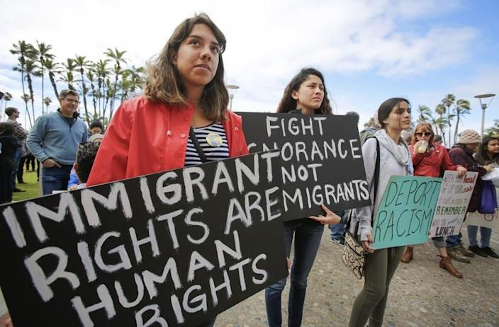 Top left: Francisca Verduzco, left, and her sister, Itzel Verduzco, center, hold signs supporting immigrant rights while attending March in Solidarity with Immigrants, San Diego. Top right: Kyle Fox, 4, and his father, Brady Fox, hold a sign at a vigil held to support the victims of the Chabad of Poway synagogue shooting. Bottom right: Emily Jones, right, and her daughters Tyra Neptune-Lucas, 12, second from right, and Lyssa Ballard, 16, center, hold signs on Espola Road to show support for Chabad of Poway. Bottom left: Kamri Jackson, center, holds up a sign as she and other people protest the Supreme Court's decision to uphold Donald Trump's travel ban while in front of the Edward J. Schwartz Federal Building in San Diego.