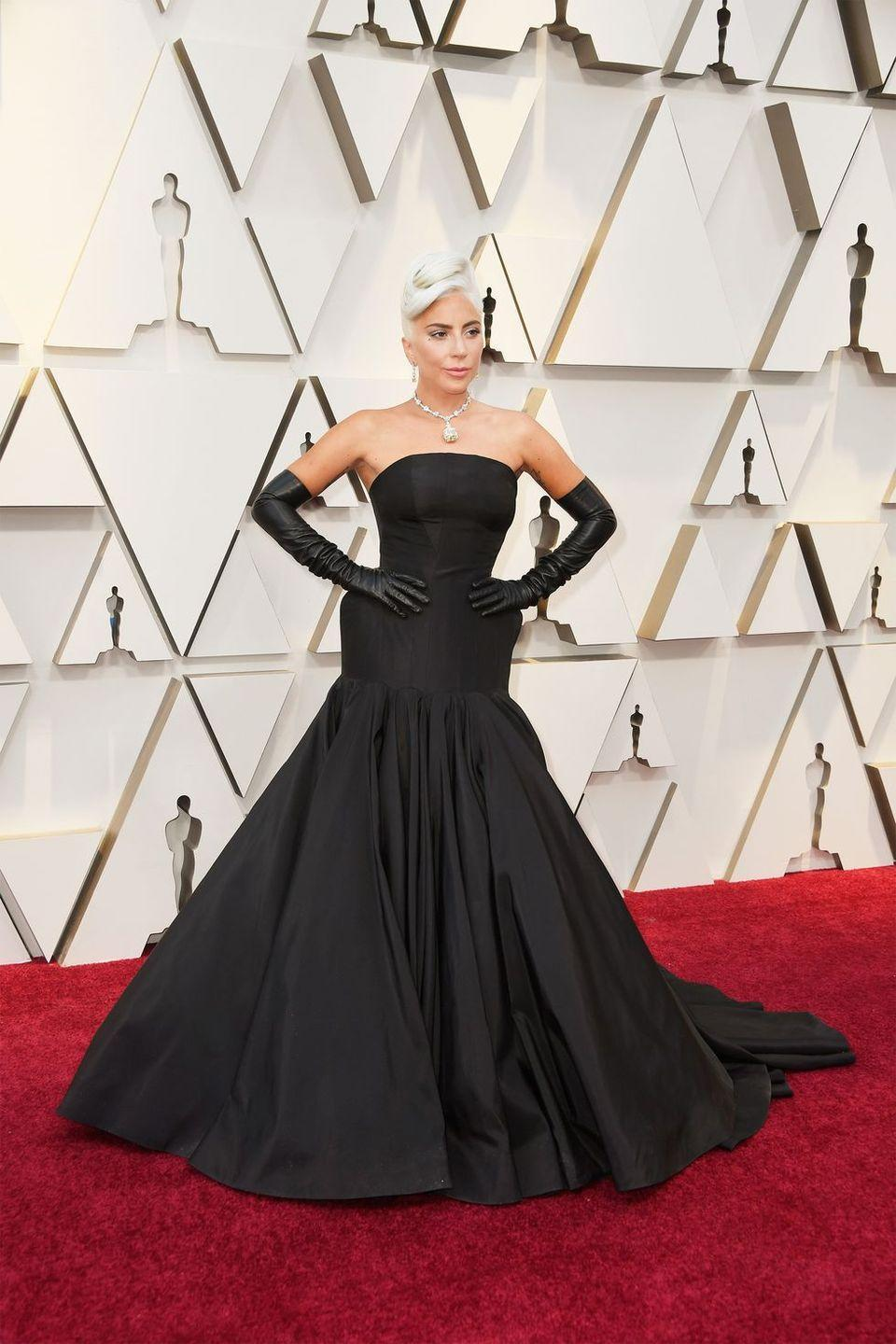 """<p>Lady Gaga <a href=""""https://www.harpersbazaar.com/celebrity/red-carpet-dresses/a26500166/lady-gaga-audrey-hepburn-oscars-2019/"""" rel=""""nofollow noopener"""" target=""""_blank"""" data-ylk=""""slk:channelled Audrey Hepburn"""" class=""""link rapid-noclick-resp"""">channelled Audrey Hepburn</a> in a breath-taking, custom, sculptural black gown by Alexander McQueen. She paired the look with a 128-carat <a href=""""https://www.harpersbazaar.com/celebrity/red-carpet-dresses/a26362164/lady-gaga-oscars-2019-tiffany-diamond/"""" rel=""""nofollow noopener"""" target=""""_blank"""" data-ylk=""""slk:Tiffany diamond necklace"""" class=""""link rapid-noclick-resp"""">Tiffany diamond necklace</a> and perfectly Gaga elbow-length black leather gloves.</p>"""