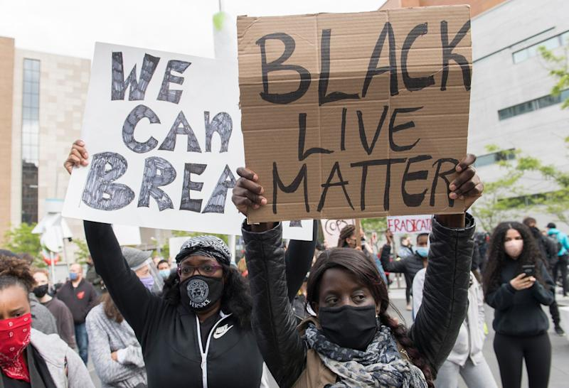 People hold up signs during a demonstration where they called for justice for George Floyd and all victims of police brutality in Montreal on May 31, 2020. (Photo: Graham Hughes/THE CANADIAN PRESS)