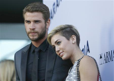 "Cast member Liam Hemsworth poses with his fiancee, singer Miley Cyrus, at the premiere of ""Paranoia"" in Los Angeles, California in this file photo taken August 8, 2013. REUTERS/Mario Anzuoni/Files"