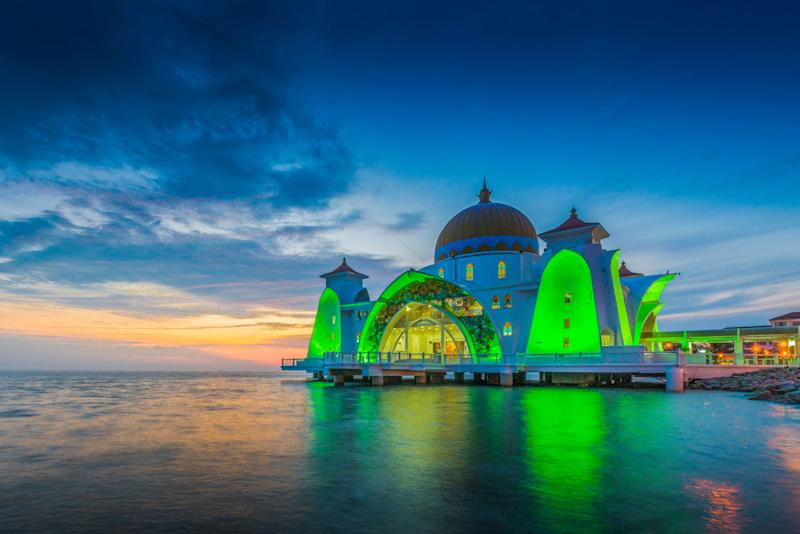 """The Malacca Straits Mosque is located on a man-made island in Malaysia. This gorgeous mosque is also called the """"<a href=""""https://melakatravel.info/what-to-do/malacca-straits-mosque-floating-mosque-melaka/"""" target=""""_blank"""">Floating Mosque</a>"""" for an illusion it gives off of sitting righton top of the water."""