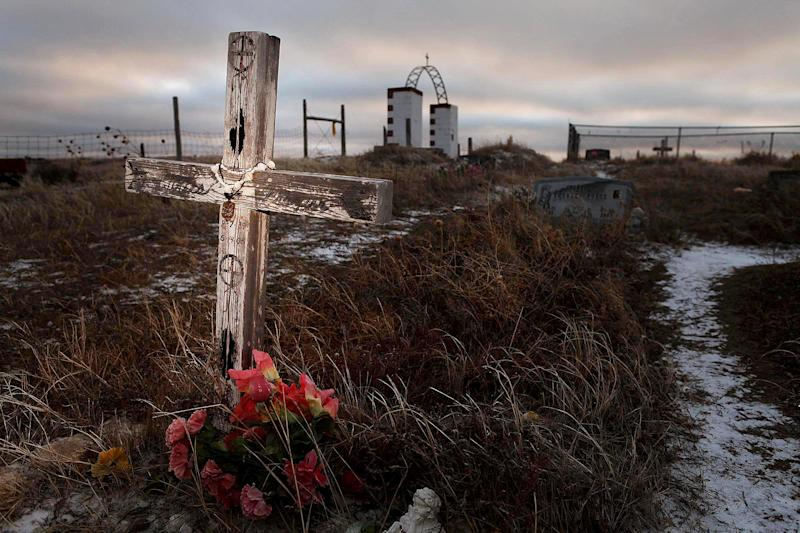 This Feb. 7, 2012 photo shows a cross on a grave at the Wounded Knee National Historic landmark in South Dakota. James Czywczynski, 74, is trying to sell a 40-acre fraction of the landmark for $3.9 million to the Oglala Sioux Tribe. But leaders on the Pine Ridge Indian Reservation say the asking price for a property appraised at less than $7,000 is just too much. The land sits adjacent to a gravesite where about 150 of the 300 Lakota men, women and children killed by the 7th Cavalry in 1890 are buried. (AP Photo/Rapid City Journal)