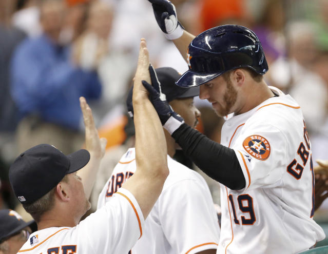 Houston Astros' Robbie Grossman (19) is welcomed back to the dugout after hitting a two-run home run against the Boston Red Sox in the second inning of a baseball game Tuesday, Aug. 6, 2013, in Houston. (AP Photo/Pat Sullivan)