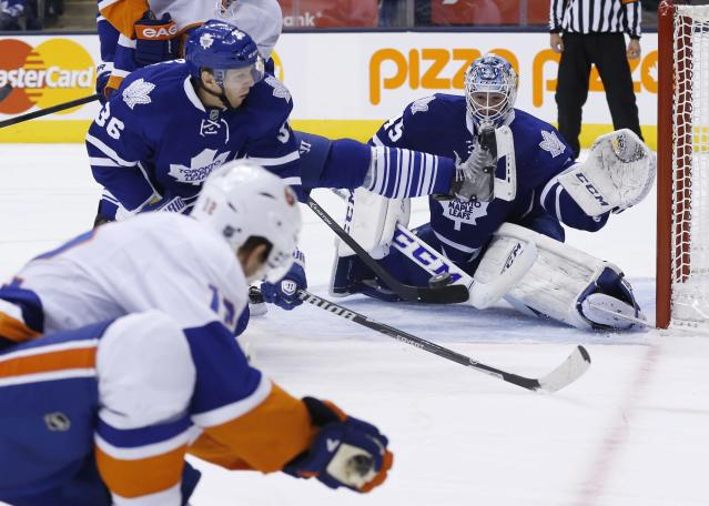 Toronto Maple Leafs goalie Jonathan Bernier makes a save with teammate Carl Gunnarsson, center, against New York Islanders' Josh Bailey, left, during the third period of an NHL hockey hockey game, Tuesday, Nov. 19, 2013 in Toronto. (AP Photo/The Canadian Press, Mark Blinch)