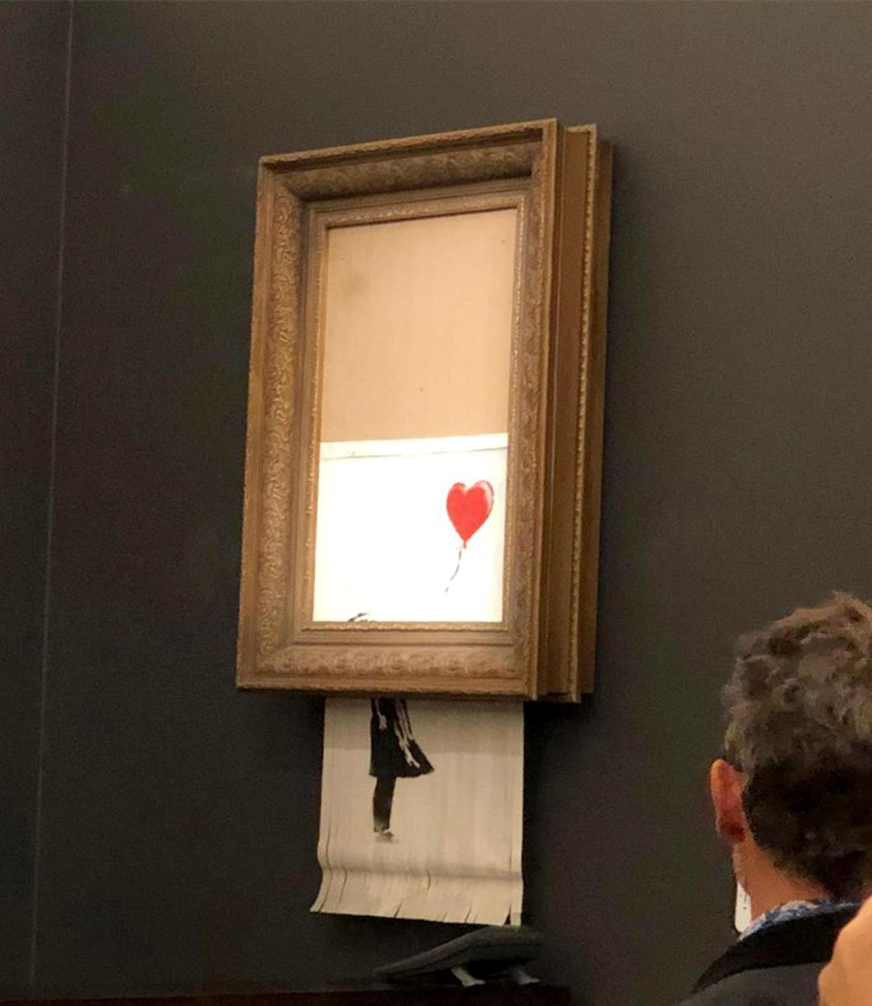 <em>'You've been Banksy'ed' – as soon as it sold, the painting suddenly passed through a shredder installed in the frame (Picture: PA)</em>