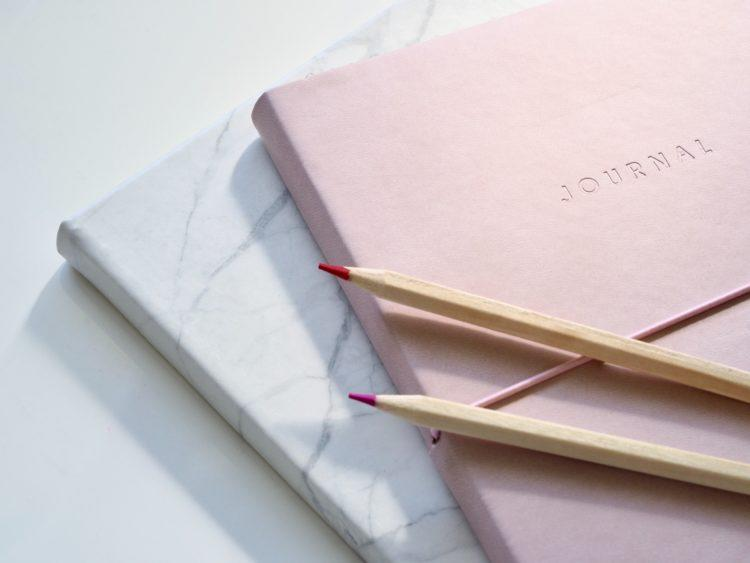 A pink journal on top of a white counter.