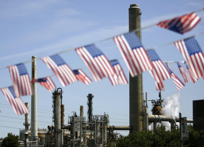 """FILE - In this April 30, 2008 file photo, American flags are seen near the Shell refinery, in Martinez, Calif. On Weds., Nov. 14, 2012, California's largest greenhouse gas emitters will for the first time begin buying permits in a landmark """"cap-and-trade"""" system meant to control emissions of heat-trapping gases and spur investment in clean technologies. The program is a key part of California's 2006 climate-change law, AB32, a suite of regulations that dictate standards for cleaner-burning fuels, more efficient automobiles and increased use of renewable energy. (AP Photo/Ben Margot, File)"""
