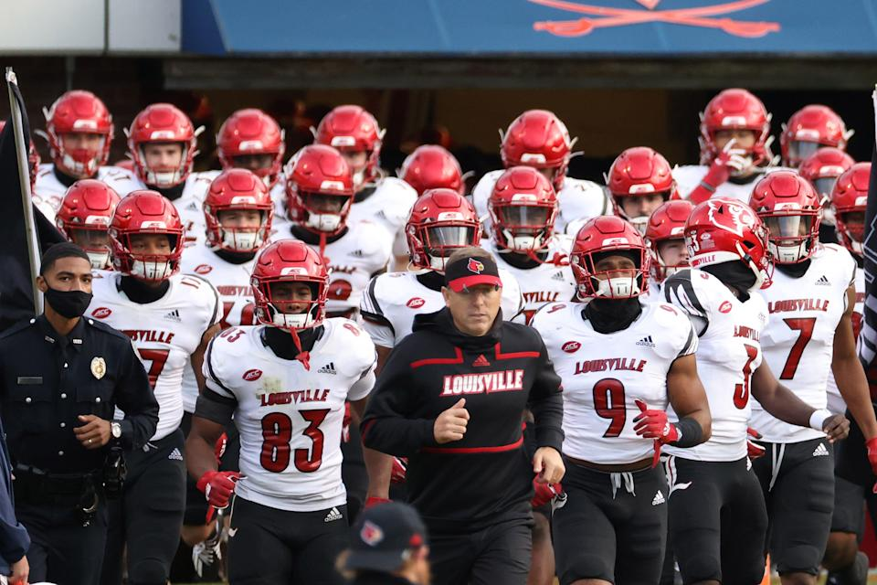 Louisville head coach Scott Satterfield, middle, and his Cardinals have a pretty challenging schedule in 2021.