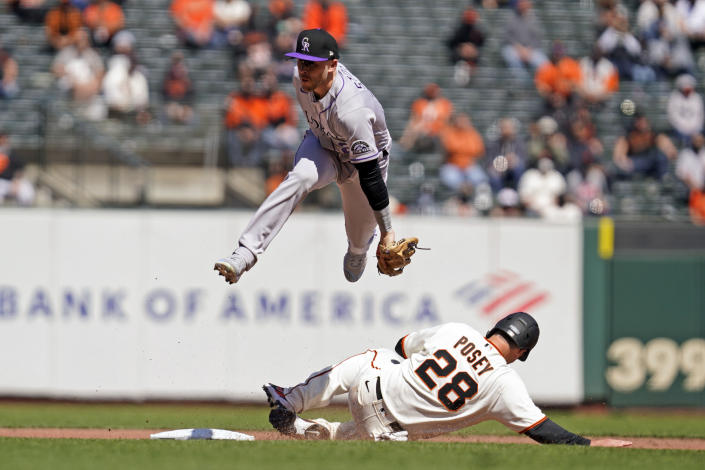 San Francisco Giants' Buster Posey is forced out at second base beneath Colorado Rockies shortstop Trevor Story on a fielder's choice hit by Mauricio Dubon during the fifth inning of a baseball game, Friday, April 9, 2021, in San Francisco. (AP Photo/Eric Risberg)