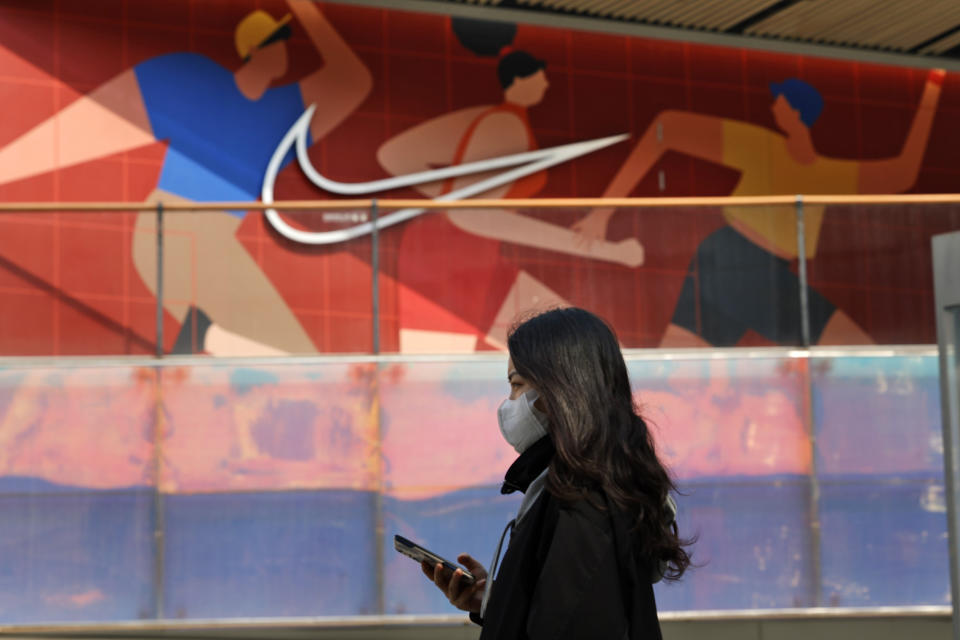 A woman wearing a mask passes by a Nike store in Beijing on Thursday, March 25, 2021. China's ruling Communist Party is lashing out at H&M and other clothing and footwear brands as it retaliates for Western sanctions imposed on Chinese officials accused of human rights abuses in the northwestern region of Xinjiang. (AP Photo/Ng Han Guan)