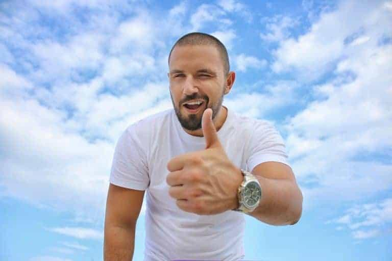 Man winking with thumbs up with blue sky in background