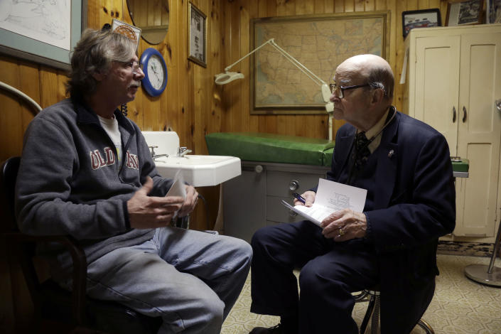 In this Tuesday, Oct. 30, 2012 photo,m Dr. Russell Dohner, right, talks with patient Joe Logsdon about his high cholesterol in Rushville, Ill. Patients line up early outside his office just off the town square, waiting quietly for the doctor to arrive, as he has done for nearly 60 years. (AP Photo/Jeff Roberson)