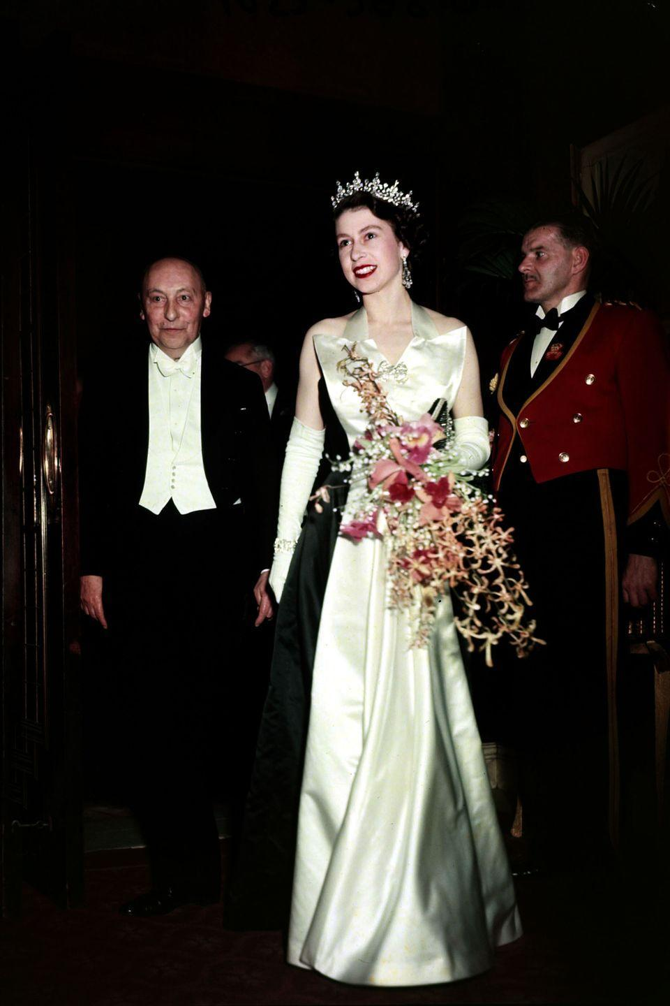 <p>The queen dons a satin sleeveless ball grown, chandelier earrings, and long satin gloves while carrying an elaborate bouquet with orchids and baby's breath.</p>