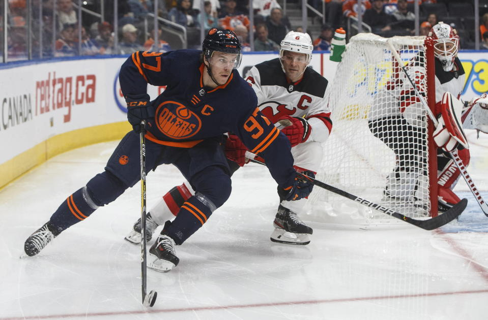 New Jersey Devils' Andy Greene (6) chases Edmonton Oilers' Connor McDavid (97) during the second period of an NHL hockey game Friday, Nov. 8, 2019, in Edmonton, Alberta. (Jason Franson/The Canadian Press via AP)