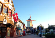 FILE - This Sept. 30, 2014 photo shows the Danish flag flying on Alisal Road in Solvang, Calif., on Sept. 30, 2014. Founded in 1911 by Danish immigrants, Solvang is a touristy enclave with Danish bakeries, Danish-themed hotels and even a Hans Christian Andersen Museum. The location is featured in a collection of mini-essays by American writers published online by the Frommer's guidebook company about places they believe helped shape and define America. (AP Photo/Solvej Schou, File)