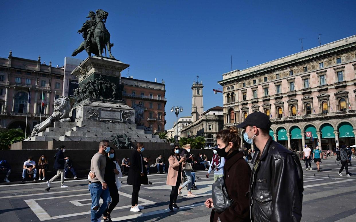 Italy's government has already made it mandatory to wear face masks outdoors. Here people walk through the Piazza del Duomo in Milan. - AFP
