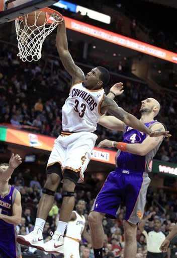 Cleveland Cavaliers' Alonzo Gee (33) dunks against Phoenix Suns' Marcin Gortat, right, during the second quarter of an NBA basketball game Tuesday, Nov. 27, 2012, in Cleveland. (AP Photo/Tony Dejak)