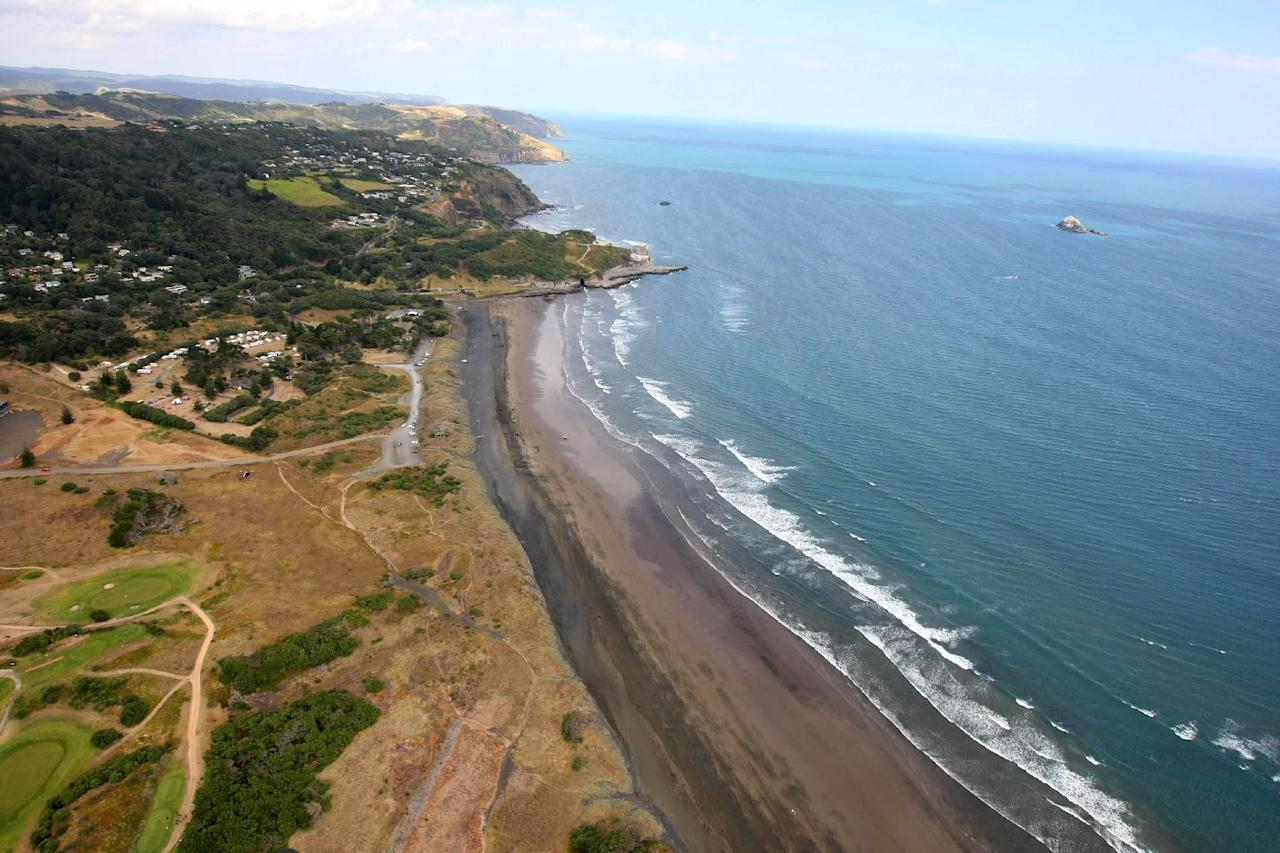 "Muriwai Beach near Auckland, New Zealand, is seen from the air Wednesday, Feb. 27, 2013, following a fatal shark attack. Police said a man was found dead in the water Wednesday afternoon after being ""bitten by a large shark."" Police and surf lifesavers recovered the man's body. The police statement said Muriwai Beach near the city of Auckland has been closed. (AP Photo/New Zealand Herald, Chris Gorman) NEW ZEALAND OUT, AUSTRALIA OUT"