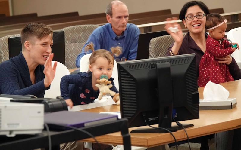 Dr. Erin Meyer and her wife Dr. Sandra Medinilla wave to family and friends that video chatted during the adoption ceremony of their fourth child 6-month-old Sydney.