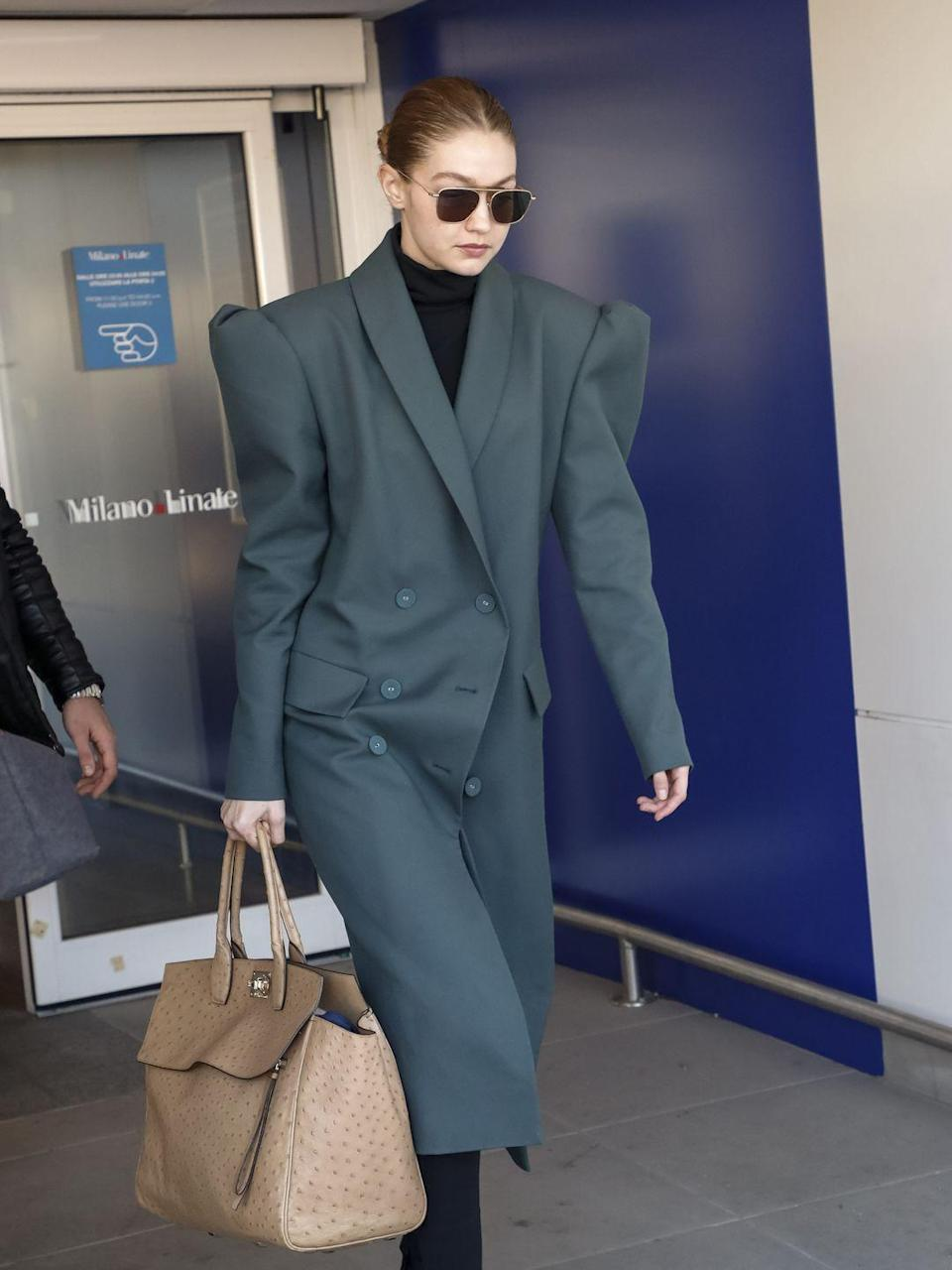<p>In a teal-gray trench coat, black turtleneck, black shades, and beige bag.</p>