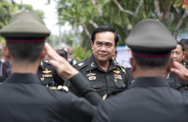 FILE - In this Thursday, Aug. 21, 2014, file photo, Thailand's Prime Minister Prayuth Chan-ocha, center, arrives for an anniversary ceremony for the 21st infantry regiment, Queen's Guard, in Chonburi Province, Thailand. Prayuth became prime minister in a very Thai way: He led a military coup. Now after five years of running Thailand with absolute power, he's seeking to hold on to the top job through the ballot box. The military's thinly veiled proxy party has put forward Prayuth as its nominee for prime minister after Sunday's election. But running the show in an elected government may not be as easy though since he'll no longer be able to muzzle opponents and rely on a rubberstamp legislature. (AP Photo/Sakchai Lalit, File)