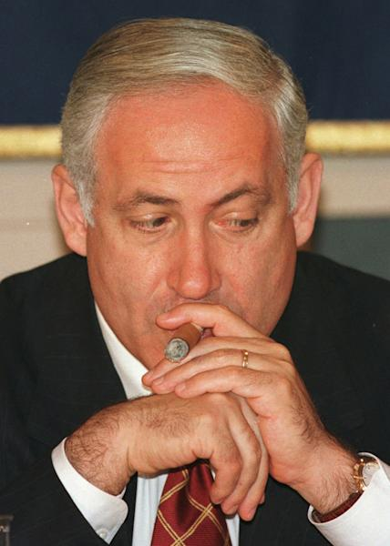 FILE In this Aug. 26 1997 file photo, Israeli Prime Minister Benjamin Netanyahu draws his cigar while pondering a question during a press luncheon at the Foreign Correspondents' Club in Tokyo. As his government is slashing welfare benefits and hiking takes for the working class to overcome a huge deficit, Israeli Prime Minister Benjamin Netanyahu is finding himself under fire again for his lavish lifestyle. (AP Photo/Itsuo Inouye, File)