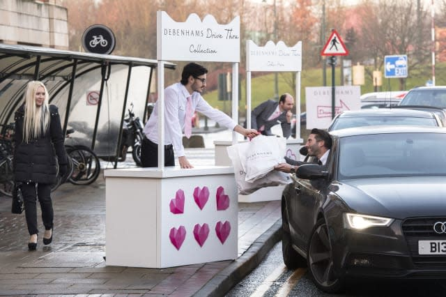 EDITORIAL USE ONLYA woman looks-on as Graig Bieszke from Manchester uses the world's first Debenhams Drive Thru, which has been created ahead of Valentine's Day, to help shoppers pick gifts for their partners at the Trafford Centre in Manchester. PRESS ASSOCIATION Photo. Picture date: Tuesday February 7, 2017. With a choice of pre-selected gifts, from lingerie to aftershave, the pilot experience guarantees shoppers will drive away with a present all without leaving the comfort of their car. Photo credit should read: Anthony Devlin/PA Wire