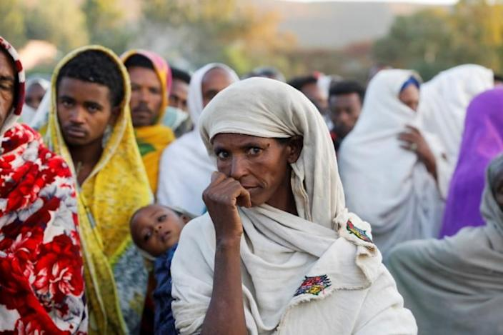 Woman stands in line to receive food donations, at the Tsehaye primary school in Shire