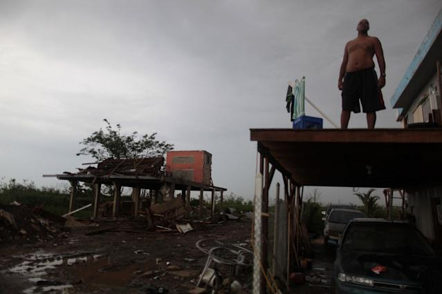 <p>A man stands on what is left of the balcony of his home and near another destroyed house, after the island was hit by Hurricane Maria in Toa Baja, Puerto Rico, Oct.16, 2017. (Photo: Alvin Baez/Reuters) </p>