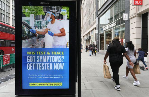 Shoppers walk past a screen on a bus stop displaying a NHS notice on test and trace on Oxford Street, London